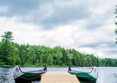 An image of the canoe docks on Saw Lake in Muskoka Ontario at the Wenonah Outdoor Education Centre.