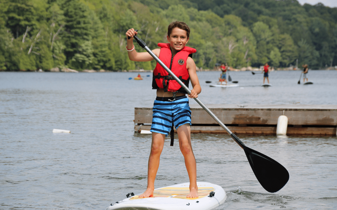An image of a Camp Wenonah camper on a paddleboard in Muskoka