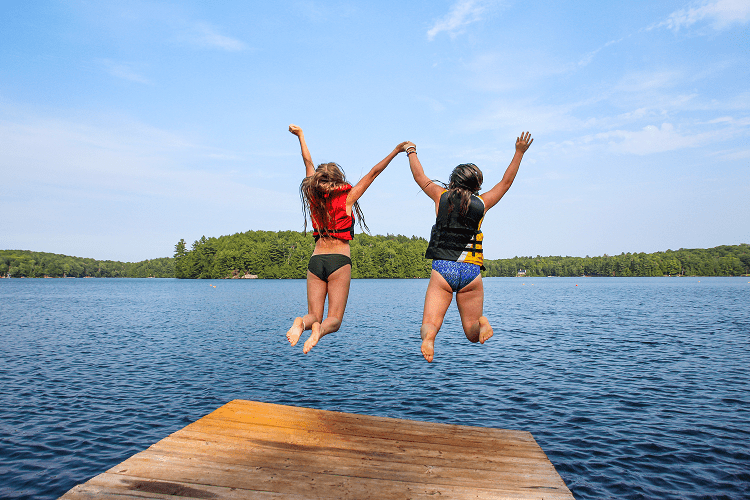 An image of campers jumping into the water at Camp Wenonah