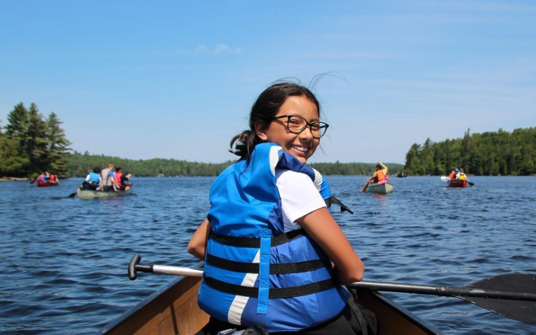 An image of a Camp Wenonah camper in a canoe in Ontario, Canada.