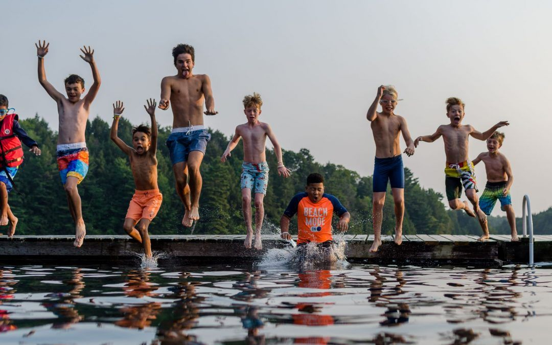 An image of campers jumping in the water at Camp Wenonah