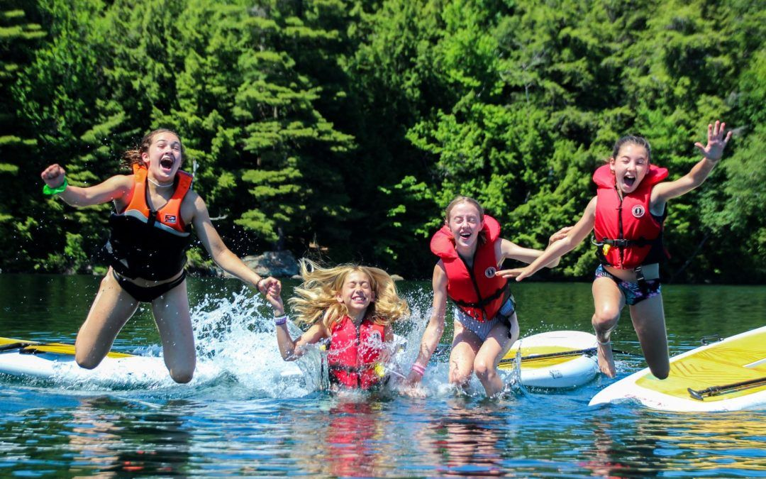 An image of campers jumping into Clear Lake at Camp Wenonah